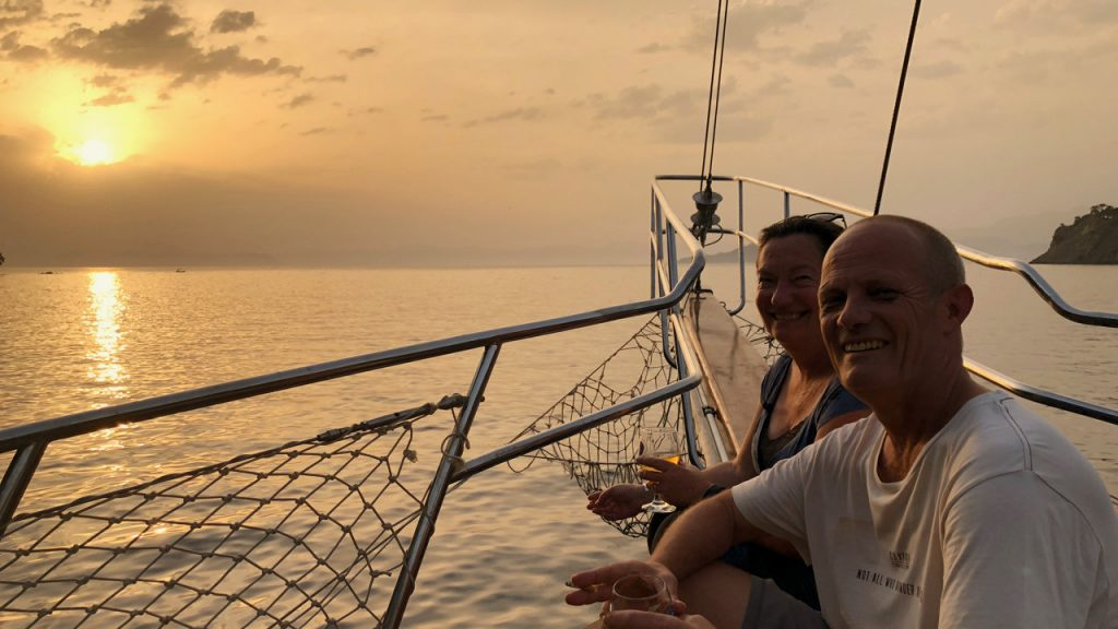 Couple at sundown in the bow of a blue cruise gullet.