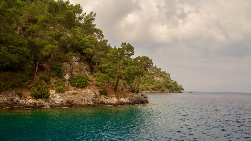Cypress covered hills meet the water in a cove on the Turkish Riviera.