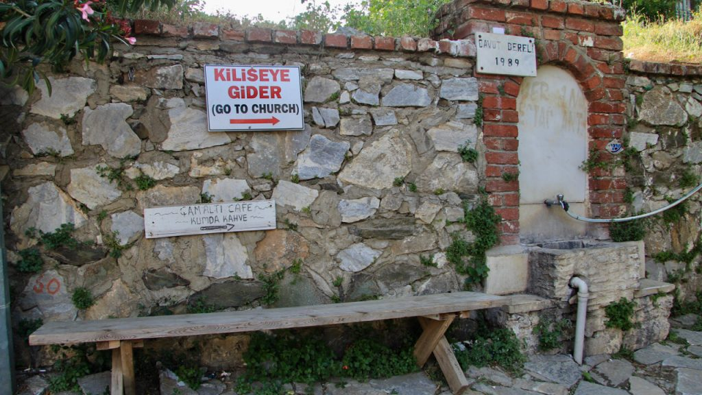 A wooden bench agains an old stone wall with a sign that says 'go to church.'