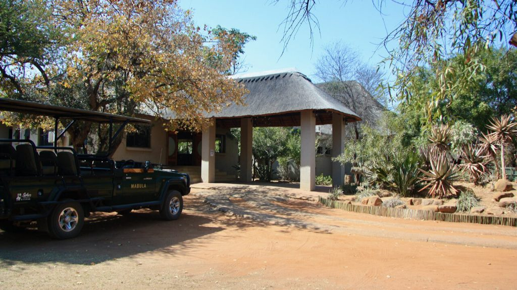 Entrance to Safari Plains Lodge with a game drive vehicle at the entrance
