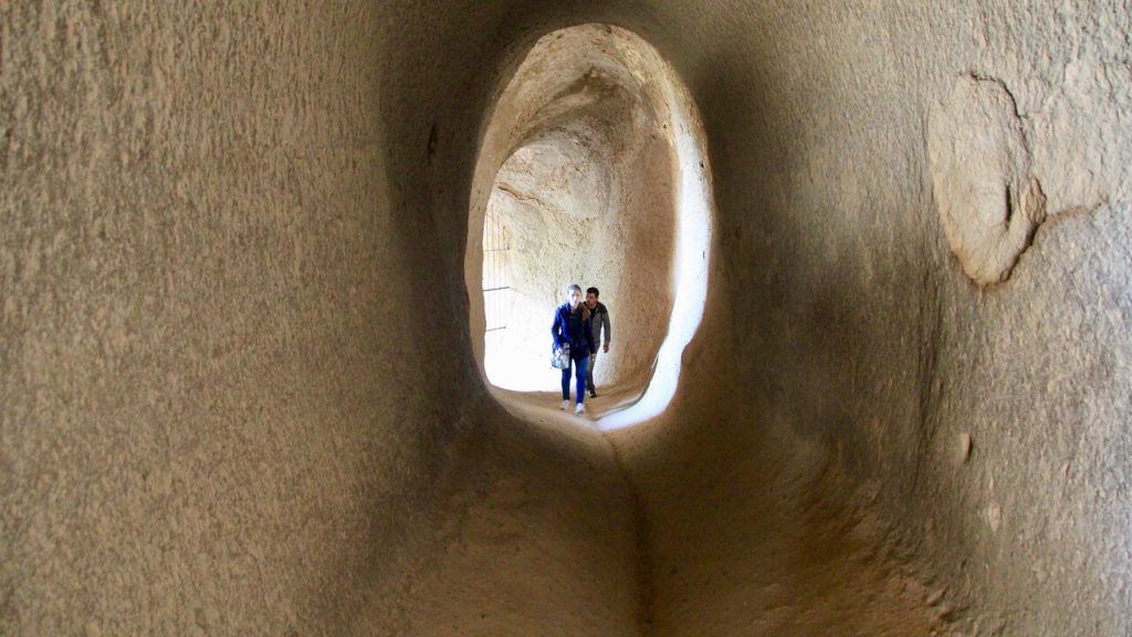 Two people in the rock hewn entrance to Selime Cathedral in Cappadocia