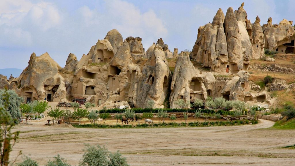 A rock cone complex with horses grazing outside in Cappadocia