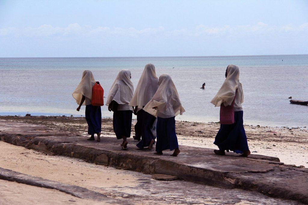 Young muslim girls walk along the Zanzibar beach